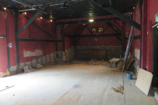 The exposed floor of the barn showing the railway track on the right running along the north wall.