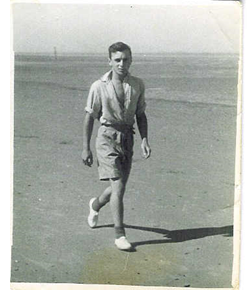 Black and white photograph of a 16 year old boy walking on the beach wearing shorts and a short sleeve shirt | Contributor