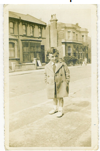 Black and white photograph of a 6 year old boy smartly dressed in a pea coat standing on the pavement with a row of shops in the background | Contributor