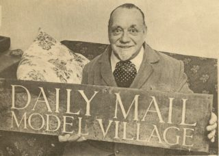 Fred Garrod and the Daily Mail Model Village sign recovered from the Handside Lane pond.   Welwyn Times & Hatfield Herald