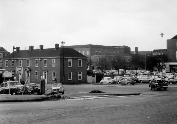 Junction of Stonehills and Bridge Road, showing old Police Station and Dickinson & Adams Motors c1962. Welwyn Stores, now John Lewis, in the background | Welwyn Garden City Library