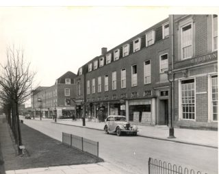 Black and white photograph of a row of shops, there is an old car parked in front of one of the store fronts | Welwyn Garden City Library